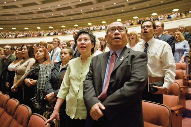 A couple standing and singing a rest hymn with the congregation during a session of general conference.