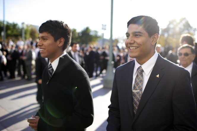 Two young men standing outside the Conference Center with other men while waiting for the priesthood session.