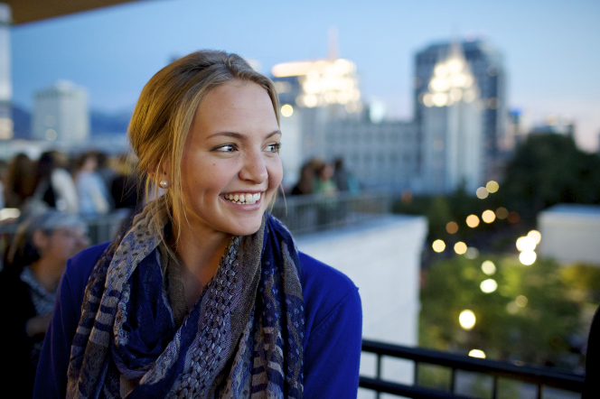 A young woman in a blue cardigan and scarf, standing on a balcony at dusk with the Salt Lake Temple rising in the distance.