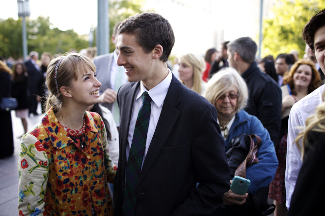 A smiling young man in a suit standing by a young woman in an orange jacket outside the Conference Center.