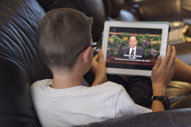 A boy sitting at home and watching President Monson speak at general conference on his tablet.