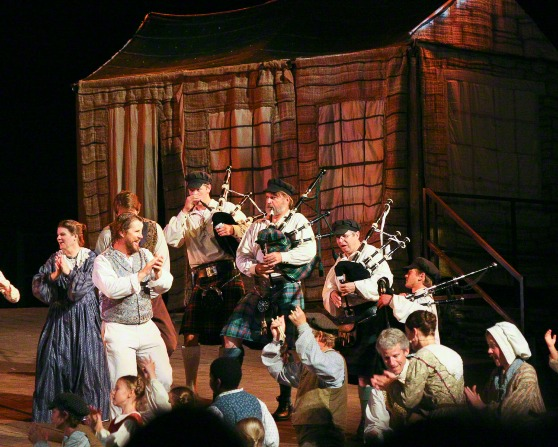 Nauvoo Pageant actors on a platform in front of a house, with four men playing bagpipes and other actors dancing.