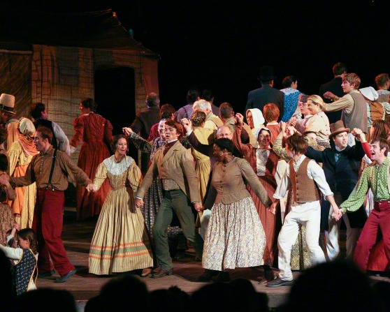 Rows of actresses and actors from the Nauvoo Pageant holding hands while dancing on stage in front of a house.