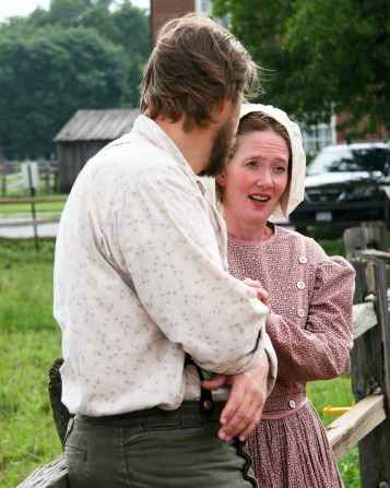 An actor from the Nauvoo Pageant leaning against a wooden fence and turning to look at an actress who is talking to him.
