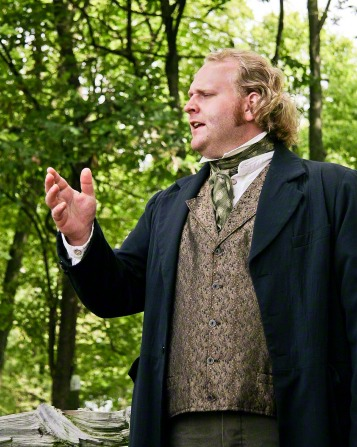A preacher in the Nauvoo Pageant wearing a green tie, brown vest, and black suit coat, standing and preaching near a group of trees.