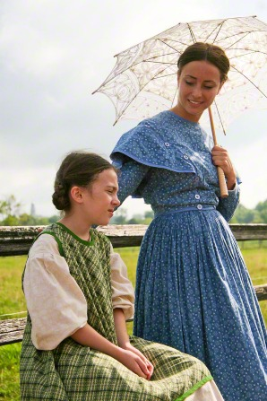 An adult actress from the Nauvoo Pageant in a blue dress, standing and holding a white umbrella while looking at a child actress who is sitting down.