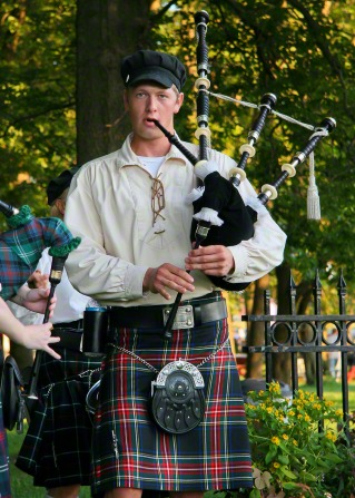 An actor from the Nauvoo Pageant in a black cap, tan shirt, and plaid kilt, standing and playing the bagpipes.
