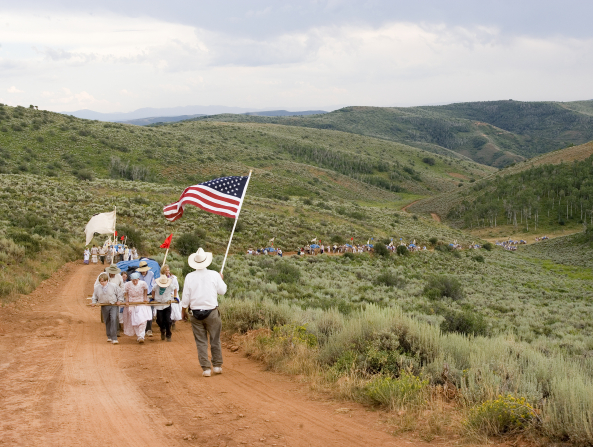A man stands and waves an American flag as he walks in front of a large group of men and women dressed as pioneers pulling handcarts up a green hill.