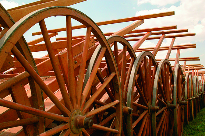 A group of several wooden handcarts all lined up together.