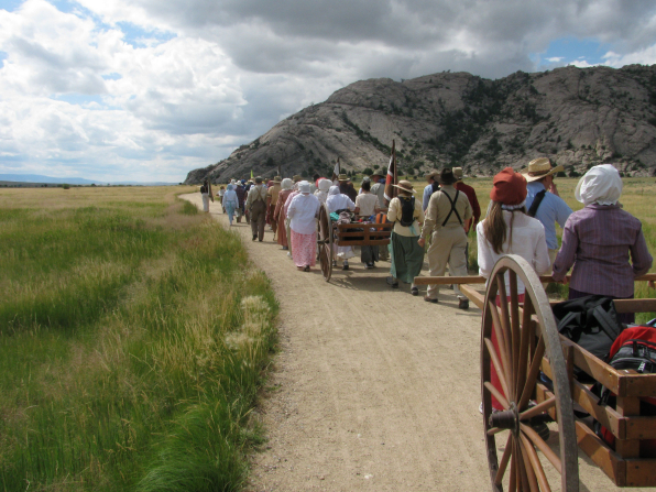 A large group of men and women, all dressed as pioneers, walk down a road past a mountain, pushing and pulling handcarts full of equipment.