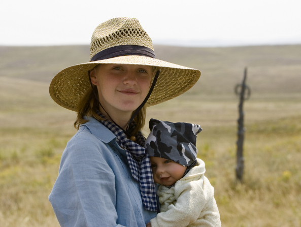 A young woman wearing a wide-brimmed straw hat, a blue button-up shirt, and a scarf stands outside in a grassy field and holds a little baby.