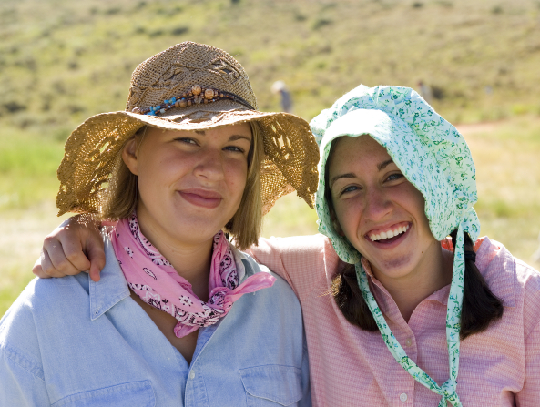 A young woman in a straw hat, pink kerchief, and blue shirt next to another young woman with pigtails, a bonnet, and a pink checkered shirt.