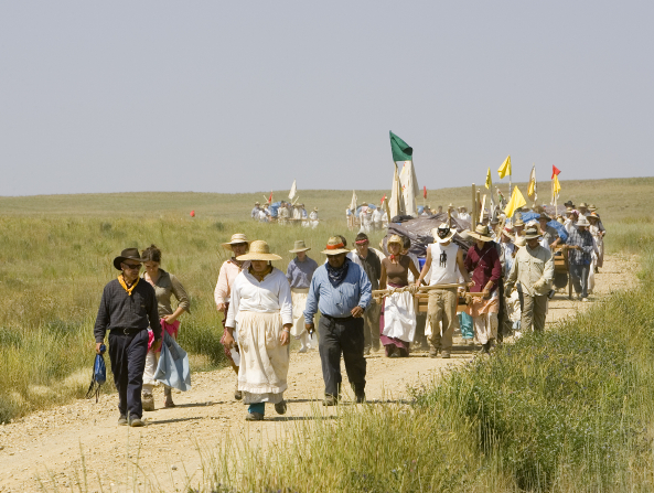 A large group of men and women, all dressed as pioneers in traditional clothing and hats, push handcarts with flags down a hill amid grassy plains.