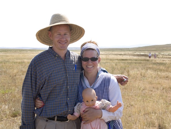 A man wearing a wide-brimmed straw hat and a plaid button-up shirt stands next to his wife, who is wearing a checkered dress and carrying a baby doll on trek.