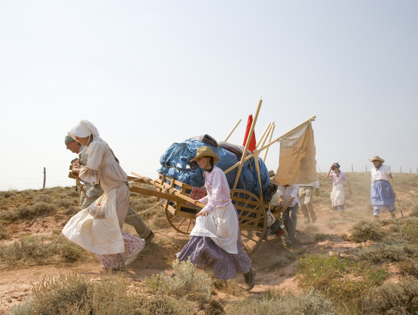 Two women wearing skirts, aprons, and hats pull a handcart full of equipment over a rocky path while other people walk behind.