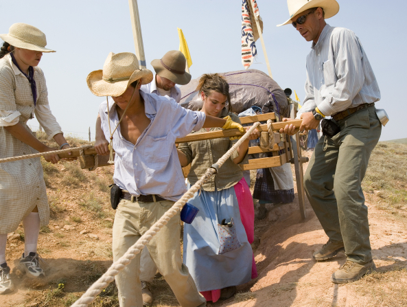 A young man in a straw hat and blue button-up shirt pulls a handcart over a rocky and jagged path with men and young women helping from behind.