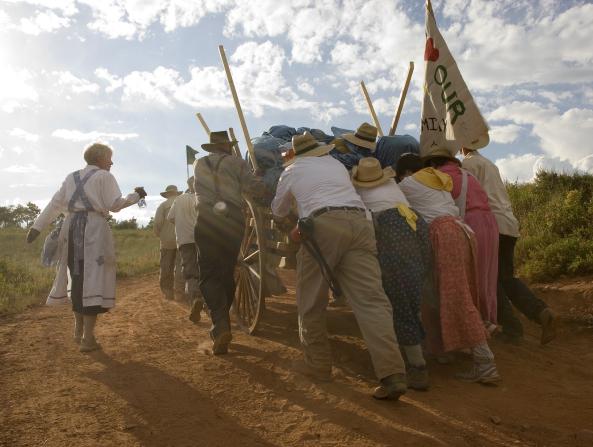 A man and three women dressed as pioneers push a handcart full of equipment while others stand on the side and help guide it over a dusty path.