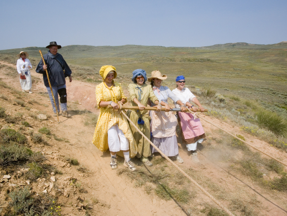 Four young women all dressed in hats, bonnets, and dresses pull back on a beam attached by ropes to a handcart as it goes downhill.
