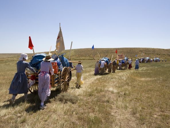 A view behind a group of young men and women dressed in pioneer clothing, pushing handcarts loaded with equipment and flags through a grassy field.