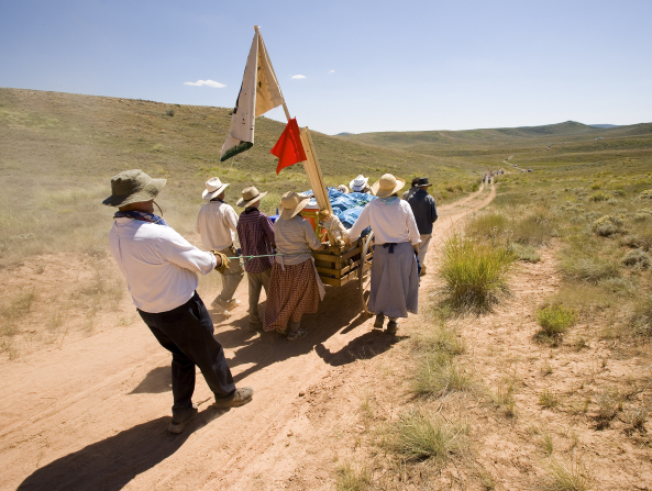 A man dressed as a pioneer pulls a rope attached to a handcart as it goes downhill, with a group of other men and women helping push the handcart.