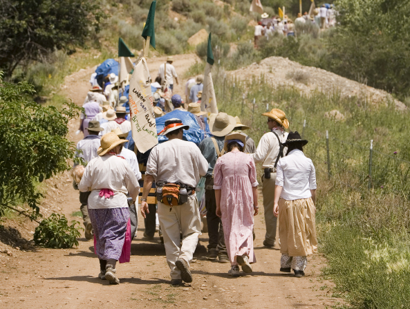 A man and three women are seen from the back walking with a large group of people, all wearing hats and dressed as pioneers, pushing handcarts.