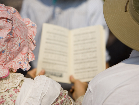 A women wearing a bonnet and a flower-patterned dress holds a hymnbook next to a man in a white shirt and wide-brimmed hat.