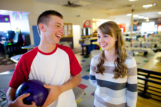 A teenage girl at a bowling alley, standing next to a teenage boy, who is laughing and holding a blue bowling ball.