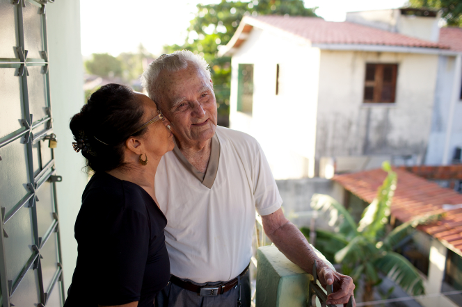 An elderly man stands outside near a building in Brazil and smiles as his wife leans forward kissing his cheek.