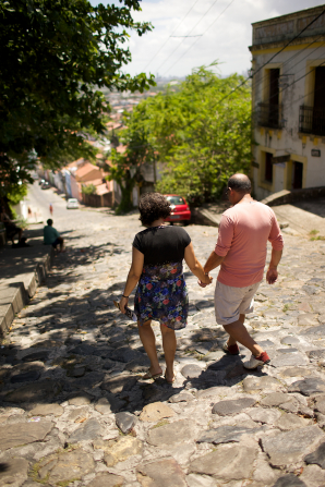A husband in a pink shirt and his wife in a dress holding hands and walking down a stone street toward houses in Brazil.