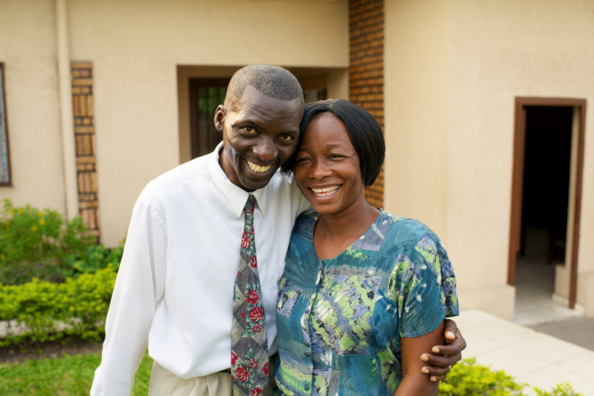 A husband and wife standing and hugging each other outside a building surrounded by green shrubs in Africa.