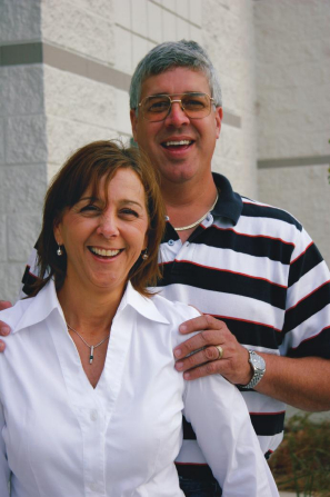 A portrait of a man in a black and white striped shirt standing behind his wife in a white shirt as they smile together.