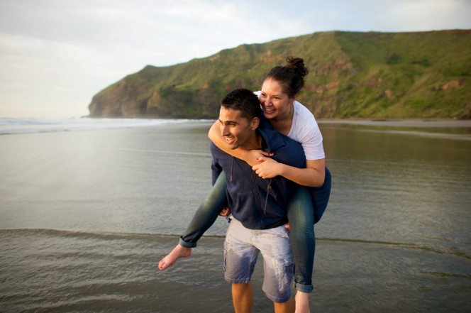 A young man standing in a blue jacket and wet shorts while carrying a barefoot young woman in a white shirt and jeans on his back at a beach in New Zealand.