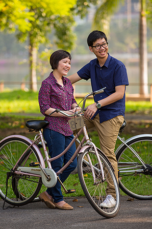 A man sitting on the seat of a bike and a woman standing next to him with another bike while looking in the distance.
