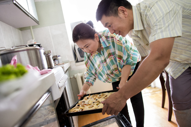 A husband and wife from Mongolia lean over and take a pan with prepared food out of the oven.