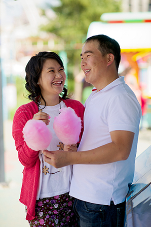 A couple from Mongolia standing and laughing together while holding pink cotton candy.