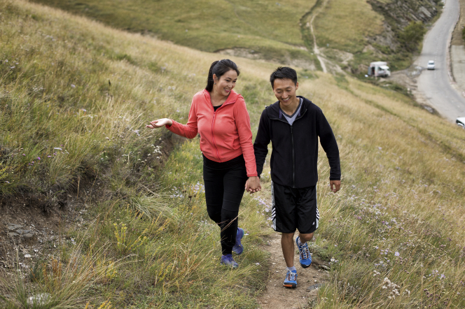 A couple from Mongolia smiling, holding hands, and wearing exercise clothes and tennis shoes while hiking up a trail with brush on each side.