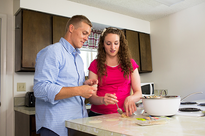 A young man and woman standing in a kitchen and preparing dinner together.