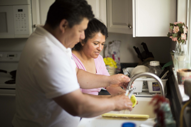 A husband and wife stand by their kitchen sink with water flowing out of the faucet as they wash dishes together.