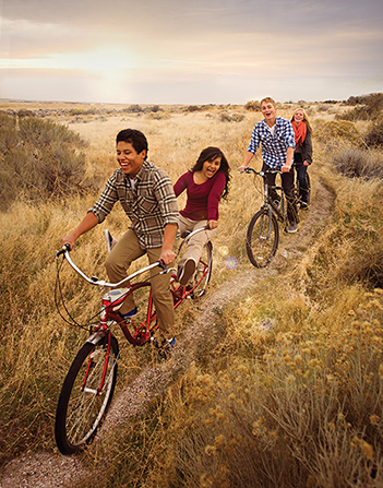 Two couples smiling while riding tandem bikes together down a narrow path with brush on either sides.