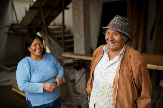 A man in a button-up shirt, brown jacket, and hat laughing and standing with his wife nearby in a long-sleeve blue shirt in a workshop in Ecuador.