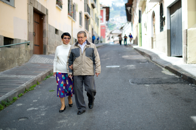 An elderly man in a jacket, pants, and dress shoes walks down a street arm-in-arm with his wife in a white sweater, floral skirt, and black shoes.