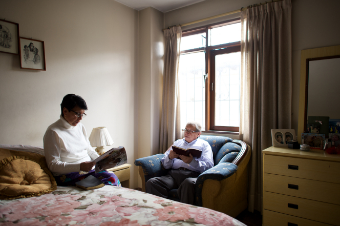 An elderly man sits on a sofa by a window while reading the scriptures, and his wife sits on their bed reading the Liahona magazine in their bedroom.