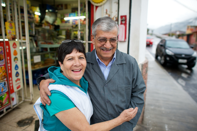An elderly husband and wife hug each other outside on the sidewalk near a store, with cars seen in the background.