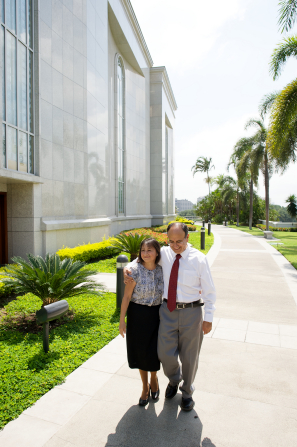 A husband wearing a white shirt, tie, and pants walks outside the Guayaquil Ecuador Temple with his arm over his wife's shoulders. She is wearing a blouse and black skirt.