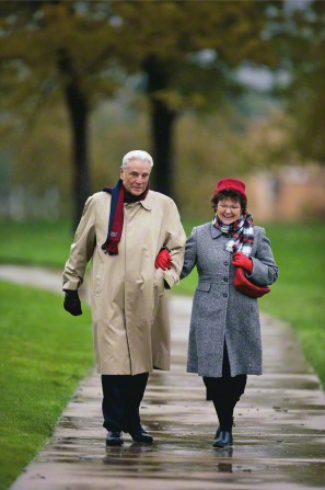 An elderly couple in coats, scarves, and gloves, walking with arms linked down a wet sidewalk.