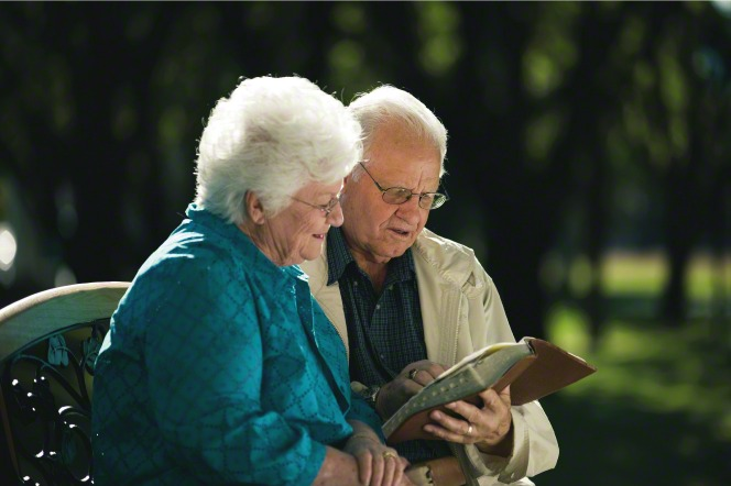 An elderly couple sits on a bench in the park and reads the scriptures together.