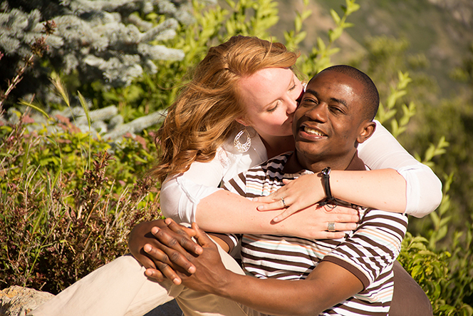 A woman sitting outside with a man while hugging him from behind and kissing his cheek in an engagement picture.