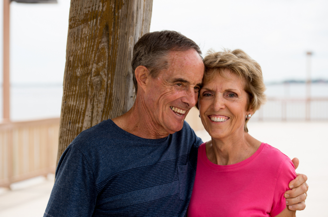 A portrait of an elderly man in a blue shirt hugging his wife, who is wearing a pink shirt, as they stand outside together.
