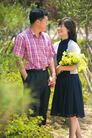 A Korean couple standing, smiling, and holding hands while the woman holds a bouquet of yellow flowers.