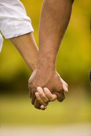 A close-up image of a man and a woman holding hands while outside, with trees faded in the background.